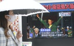 People walked past a TV screen in Tokyo showing the image of Hideki Matsuyama on Monday.