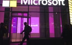 FILE - In this Nov. 10, 2016, file photo, people walk near a Microsoft office in New York. Microsoft, on an accelerated growth push, is buying speech
