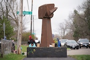 Marissa Tappy prayed Monday afternoon at the base of the fist, first installed at George Floyd Square.