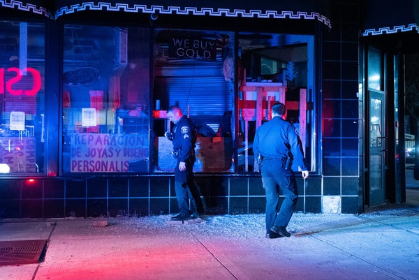 Minneapolis police officers check a damaged building on Lake Street early Monday, April 12, after Brooklyn Center Police fatally shot 20-year-old Daun