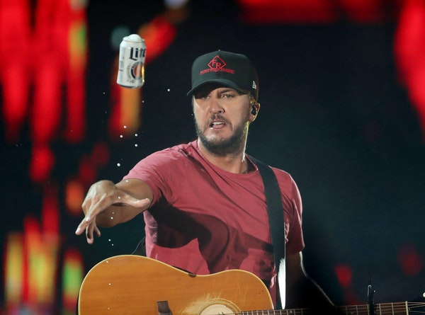 Luke Bryan tossed a cold one into the crowd while performing Saturday, July 21, 2018, at Target Field in Minneapolis.