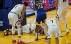 Players watch as Denver Nuggets guard Jamal Murray remains on the floor after being injured late in the second half against the Warriors on Monday.