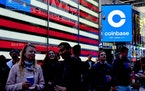 Coinbase employees gather at Times Square in New York on Wednesday, April 14, 2021, for the company's initial public offering.