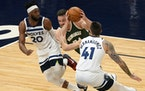 Milwaukee Bucks' Pat Connaughton, center, drives between Minnesota Timberwolves' Josh Okogie, left, and Juancho Hernangomez in the first half