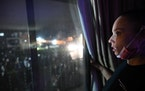 Angela Johnson, who lives across the street from the Brooklyn Center Police Department, watches the chaos from her window Wednesday night.