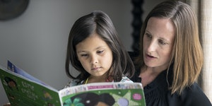 """Jenna Cruz and her daughter Esme, 6, of Chaska looked through the book """"Esme the Emerald Fairy,"""" whose main character is a youngster of color."""