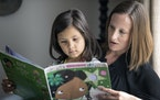 "Jenna Cruz and her daughter Esme, 6, of Chaska looked through the book ""Esme the Emerald Fairy,"" whose main character is a youngster of color."