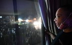 Angela Johnson, a resident across street from police department, watches chaos from her window. Johnson has been trying to study psychology and wants