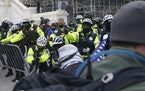 In this Wednesday, Jan. 6, 2021, photo, rioters try to break through a police line on the West Front of the Capitol, in Washington.