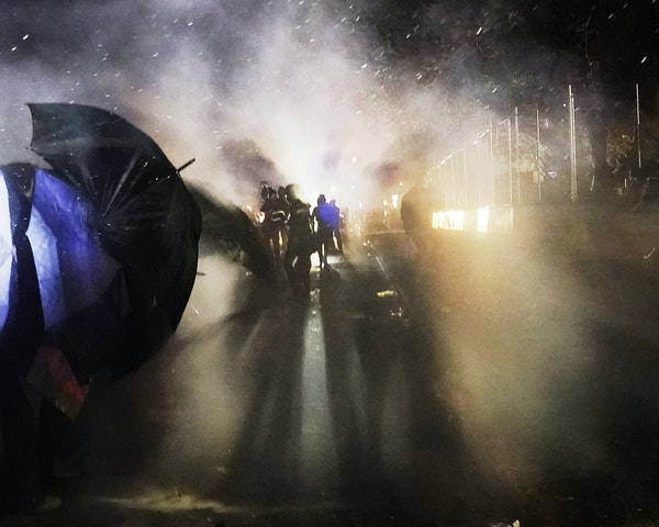 Protesters walk amid tear gas launched by nearby law enforcement officers outside the Brooklyn Center Police Department during the third night of unre