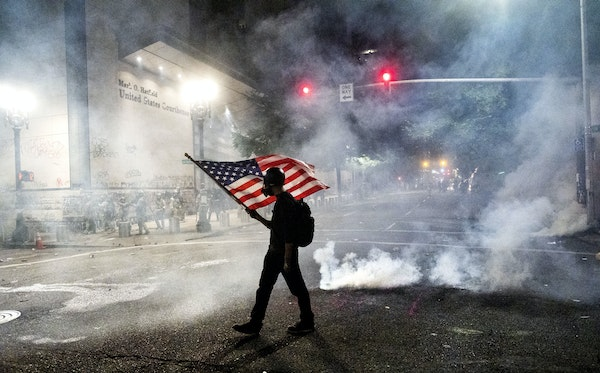 A Black Lives Matter protester carries a flag as tear gas fills the air in Portland, Ore., on July 21, 2020.