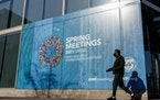 A poster is displayed on the International Monetary Fund building, Monday, April 5, 2021, in Washington.