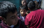 In this Feb. 13, 2020, photo, Central American migrants sent from the United States walked out into the open air after arriving in Guatemala City. Man