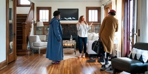 Real estate agent Leah Drury greeted prospective buyers as they arrived at an open house she held Wednesday evening in South Minneapolis .       ] GLE