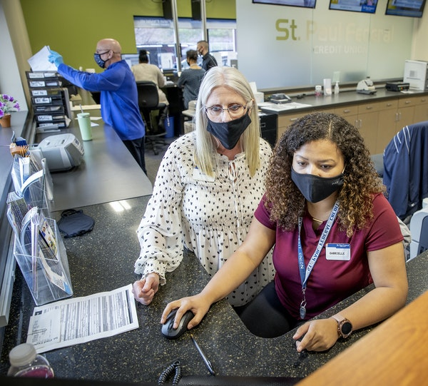 Tellers Kathy Romero,  left, and Gabrielle Kohlmeier handle accounts at the St. Paul Federal Credit Union.