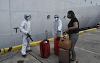 A health care worker disinfects the luggage of an evacuee before boarding the Royal Caribbean cruise ship Reflection, in Kingstown, on the eastern Car