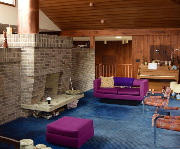 The living room has a dramatic two-sided brick fireplace with a cantilevered hearth.