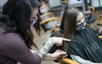 Hairstylist Josie Sottosanti used a comb to measure Amelia Kuester's hair before cutting it.