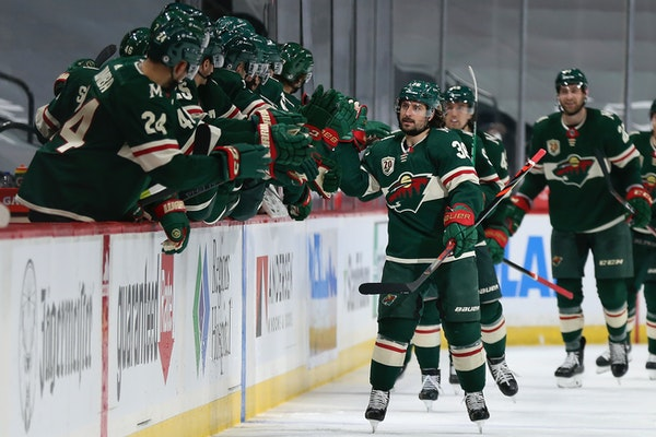 Wild's Mats Zuccarello high fives teammate on the bench in celebration after his goal against the San Jose Sharks