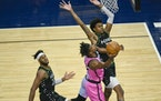 Miami forward Jimmy Butler goes up for a shot past Minnesota Timberwolves forward Jaden McDaniels