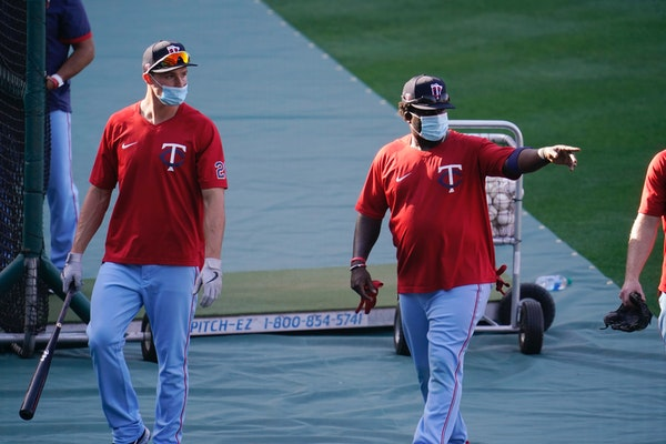 Twins players wear masks during batting practice amid the COVID-19 pandemic, before a game against the Angels on Friday