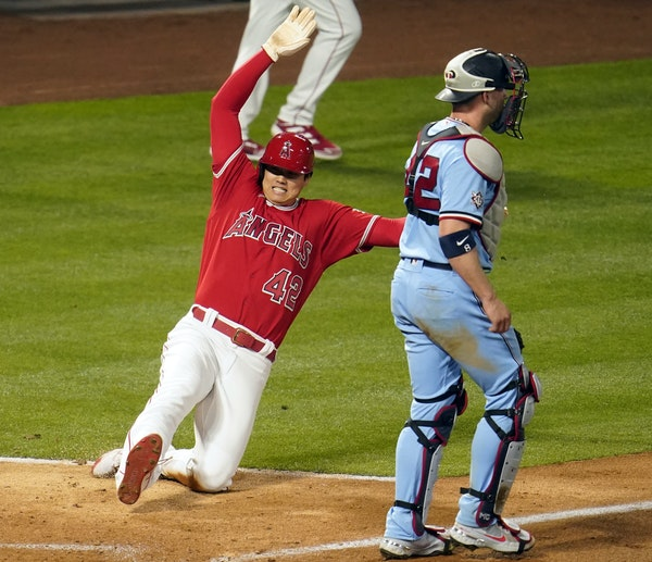 Los Angeles Angels' Shohei Ohtani scores past Minnesota Twins catcher Mitch Garver on a single from Mike Trout during the sixth inning of a baseball