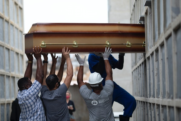 The remains of a woman who died from complications related to COVID-19 were placed into a niche April 13 by cemetery workers and relatives at the Inah