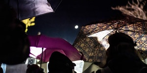 Protesters hid under umbrellas outside the Brooklyn Center Police department on Friday.