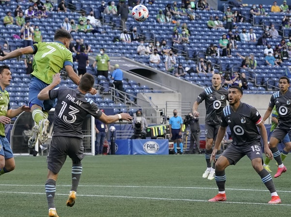 Seattle midfielder Cristian Roldan (7), checked by the Loons' Ethan Finlay, hit a header Friday during the Sounders' 4-0 victory in the season ope