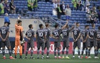 Minnesota United's Dayne St. Clair (97), Hassani Dotson (31), and Romain Metanire (19) raise their fists during the national anthem before the team�