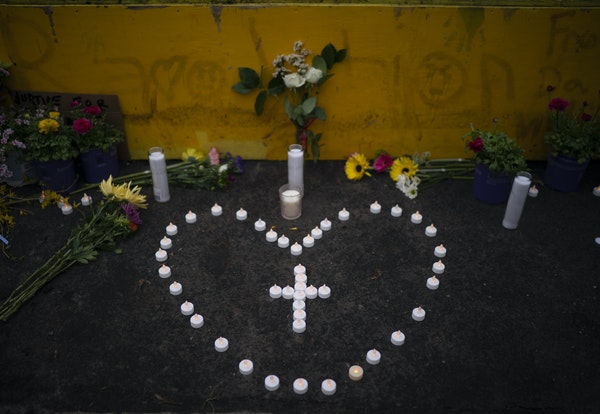 Candles at the base of the fist sculpture that is now installed at the place where Daunte Wright was killed by a Brooklyn Center police officer.