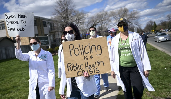 Health care workers, including University of Minnesota psychologist Christine Conelea, center, marched along Humboldt Avenue N. toward the Brooklyn Ce