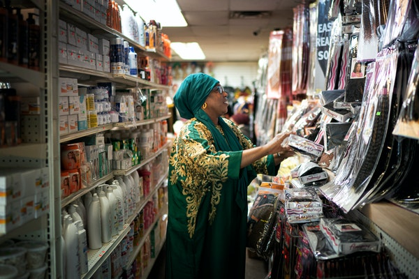 Hajah Konneh, owner of M and B Hair Braiding and Beauty Supply, tidied shelves in her Brooklyn Center store. She is still open, but not many customers