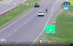 Video from the Minnesota Department of Transportation showed the man leaping out of a moving white car, then running along the median and into traffic