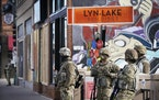 Minnesota National Guard members patrol Lyndale Avenue S. near Lake Street. There are signs of militarization throughout the city: barricades, barbed