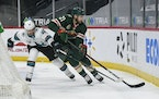 Sharks defenseman Erik Karlsson, left, and Wild defenseman Carson Soucy battled for the puck during the first period of Minnesota's 5-2 victory at X