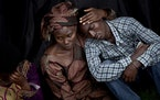 FILE - In this Monday, April 7, 2014 file photo, Bizimana Emmanuel, who was born two years before the genocide, is consoled by an unidentified woman w