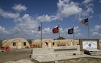 FILE - In this April 18, 2019, file photo, in this photo reviewed by U.S. military officials, flags fly in front of the tents of Camp Justice in Guant
