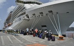 British, Canadian, and U.S. nationals line up alongside the Royal Caribbean cruise ship Reflection to be evacuated free of charge, in Kingstown on the