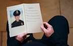 A U.S. Capitol Police officer holds a program picturing fellow officer Brian Sicknick, as Sicknick's body lay in honor in the building's Rotunda,