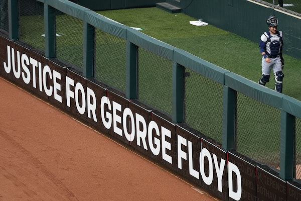 A sign calling for justice for George Floyd sat in the outfield outside the bullpen during the Twins home opener against the Seattle Mariners