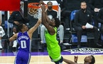 Timberwolves forward Anthony Edwards dunks as Kings guard Tyrese Haliburton defends during the first quarter