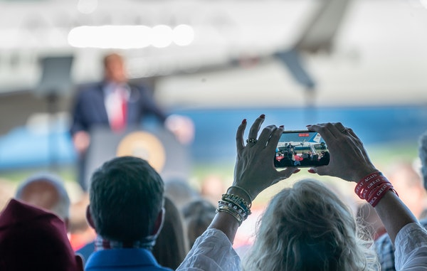 A Trump supporter recorded video as President Donald Trump delivered remarks to an invitation-only crowd at North Star Aviation in Mankato in August 2