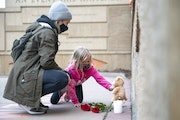 Sam Nelson and her six-year-old daughter, Kadence, from Superior, Wis., laid roses, a lit candle and a teddy bear at the base of the Clayton Jackson M