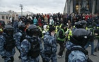 Police officers surround protesters during the opposition rally in support of jailed opposition leader Alexei Navalny in Moscow, Russia, Wednesday, Ap
