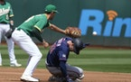Minnesota Twins' Brett Rooker slides into second base before the tag of Oakland Athletics first baseman Matt Olson (28) during the second inning