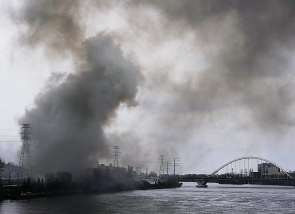 A large plume of smoke from a fire burning at Northern Metal Recycling drifted over the Mississippi River on Wednesday.