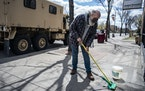 Kent Cooper cleaned up the sidewalk in front of ZRS Fossils and Gifts near a National Guard truck in Minneapolis on Wednesday.