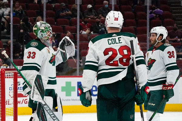 Wild goalie Cam Talbot celebrates a win against the Arizona Coyotes with defenseman Ian Cole (28) and right wing Ryan Hartman (38)