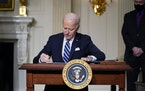 FILE - In this Jan. 27, 2021 file photo, President Joe Biden signs an executive order on climate change, in the State Dining Room of the White House i